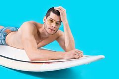 Attractive surfer lying on the board. Handsome surfer lying on the surf in studio on blue background smiling, touching hair with hand looking to camera Stock Photos