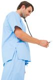 Handsome surgeon in blue scrubs using stethoscope Royalty Free Stock Photo