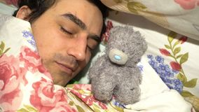 Handsome sweetheart man sleeping with plush toy, sensitive spinless tenderness loneliness, soft character. Video stock video