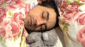 Handsome sweetheart man sleeping with plush toy, sensitive spinless tenderness loneliness, soft character. Video stock footage