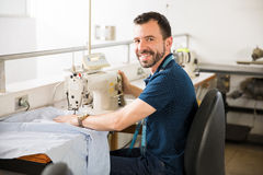Handsome tailor doing some work. Portrait of a good looking young Latin tailor using a sewing machine for work and smiling Royalty Free Stock Photo