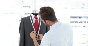 Handsome tailor measuring suit on mannequin