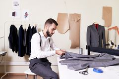 Handsome Tailor Working in Atelier. Side view portrait of handsome young man sewing bespoke suit at table in traditional atelier studio Stock Images