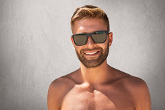 Handsome tanned man with trendy hairdo, bristle, standing topless, demonstrating his muscular body, wearing sunglasses, having ple royalty free stock images