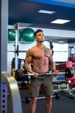 Handsome tattooed guy training with barbell Royalty Free Stock Photography
