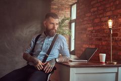 Handsome tattooed hipster in a shirt and suspenders sitting at the desk with a computer, looking out the window in an Royalty Free Stock Photo
