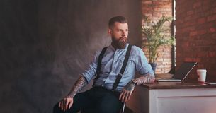 Handsome tattooed hipster in a shirt and suspenders sitting at the desk with a computer, looking out the window in an Stock Images