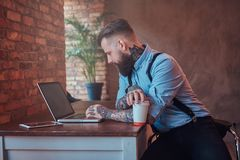 Handsome tattooed hipster in a shirt and suspenders sitting at the desk, working on a laptop, holds takeaway coffee in Stock Photo
