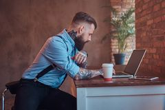 Handsome tattooed hipster in a shirt and suspenders sitting at the desk, working on a laptop, holds takeaway coffee in Stock Photos