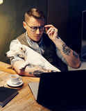 Handsome tattooed man in eyeglasses working at home on laptop while sitting at the wooden table with cute dog on his Stock Images