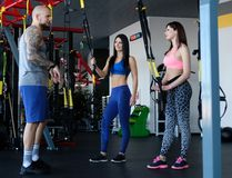 Handsome tattooed trainer explains to two young girls how to do the exercises correctly with functional loops in the gym. Tattooed trainer explains to two young royalty free stock photo