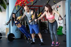 Handsome tattooed trainer explains to two young girls how to do the exercises correctly with functional loops in the gym. Tattooed trainer explains to two young stock photos