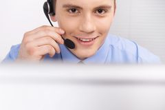 Handsome technical support operator working on computer. Royalty Free Stock Photography