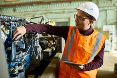Handsome Technician Adjusting Engine Features. Talented young technician wearing reflective vest and hardhat adjusting engine features of tractor with help of Royalty Free Stock Image