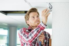 Handsome technician installing camera. Fitting Stock Photos