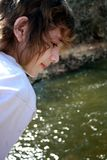 Handsome teen boy. Boy in soft focus on bridge over river Royalty Free Stock Photo