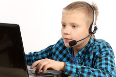 Handsome Teen Boy With Laptop Computer. And headphones with microphone on head Stock Image