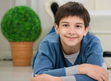 Handsome teen boy lying on floor. At home Stock Photography