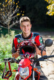 Handsome teen boy in motocross outfit. Close up outdoor portrait of handsome teen boy sitting on motocross motorcycle and wearing sport outfit Stock Photos