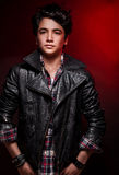 Handsome teen boy. Handsome boy portrait over red background, wearing leather jacket and stylish shirt, fashionable autumn clothes, funky teens fashion Royalty Free Stock Photo