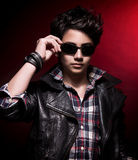 Handsome teen boy. Portrait of handsome teen boy wearing stylish sunglasses and leather jacket over dark red background, teenage fashion and style Stock Images