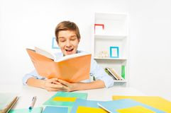 Handsome teen boy read a book sitting at home. Cute handsome boy with yellow book study at home with book filled with textbooks Royalty Free Stock Image