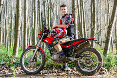 Handsome teen boy sitting on motocross motorbike. Portrait of attractive teen boy sitting on motocross motorbike in woods Royalty Free Stock Photography