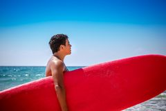 Surfer on the beach. Handsome teen boy standing on the beach with a red surfboard, happy active lifestyle, enjoying watersport, spending summer vacation near the Royalty Free Stock Photos