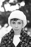 Handsome teen boy in white fur hat. Outdoors winter portrait of handsome teen boy in white fur hat Royalty Free Stock Image