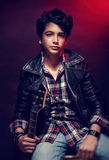Handsome teen guitarist. Portrait of handsome teen guitarist posing over dark red background, wearing trendy shirt and leather coat, cool teen's hobby Royalty Free Stock Images