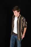 Handsome teen model. Handsome teen boy in jeans looking down on black background Stock Image
