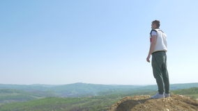 Handsome teenage boy admiring the view from a mountain top stock video