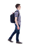 Handsome teenage boy with backpack walking isolated on white. Background Stock Photo