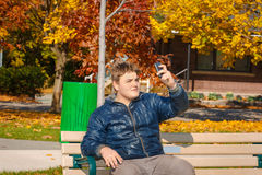 Handsome teenage boy sitting on the bench in park and making self photograph on his cellphone Stock Images