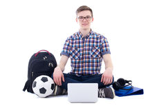 Handsome teenage boy sitting with laptop, backpack and soccer ba Royalty Free Stock Photo