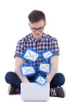 Handsome teenage boy sitting with laptop and sending messages is. Olated on white background Stock Photo