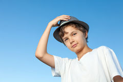 Handsome teenage boy standing outside against a blue sky Royalty Free Stock Image