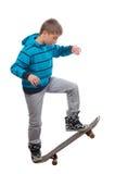 Handsome teenage skateboarder posing. Handsome teenage skateboarder balancing on the skateboard Stock Image