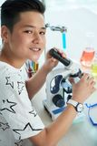 Teenage Student Posing for Photography. Handsome teenage student looking at camera with toothy smile while using modern microscope at chemistry classroom Royalty Free Stock Images