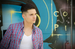 Handsome teenager against colorful graffiti wall. Handsome young man against colorful graffiti covered wall Stock Photo