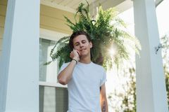 American hipster talks on the phone. Handsome teenager sets up a meeting and chats on the phone while hangs out on the porch of his victorian house stock image