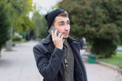 Handsome teenager talking on a mobile phone. Handsome teenager talking on a mobile phone outdoors Stock Images