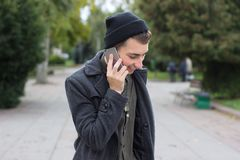 Handsome teenager talking on a mobile phone. Handsome teenager talking on a mobile phone outdoors Royalty Free Stock Photo