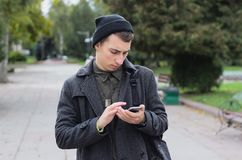 Handsome teenager texting on a mobile phone. Outdoors Royalty Free Stock Image