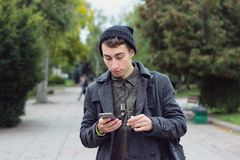 Handsome teenager texting on a mobile phone. Outdoors Stock Photography