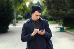 Handsome teenager texting on a mobile phone. Outdoors Stock Photos