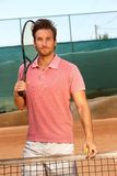 Handsome tennis player on hard court. Handsome tennis player standing on hard court holding tennis racket Royalty Free Stock Photo