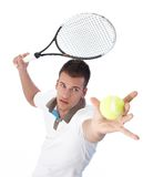 Handsome tennis player serving. Handsome young tennis player serving, concentrating Stock Photography