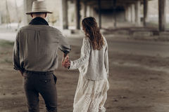 Handsome texas cowboy man in white hat holding hands with beauti. Handsome texas cowboy men in white hat holding hands with beautiful gypsy women in white dress Stock Image