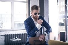 Handsome thinker. Good looking young man in full suit and eyewear keeping hands clasped while sitting on the stool royalty free stock photo